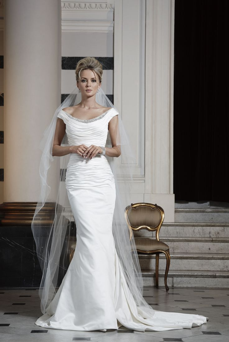 The simplicity of this statuesque mermaid gown gives it a timeless essence. The finely draped portrait neckline and bodice will shape your figure beautifully, making you feel supremely confident in your wedding gown.