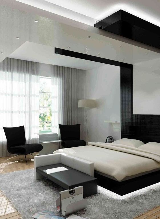 This master bedroom features cool tones of black, gray and white as well as a contemporary take on a tray ceiling with lighting.