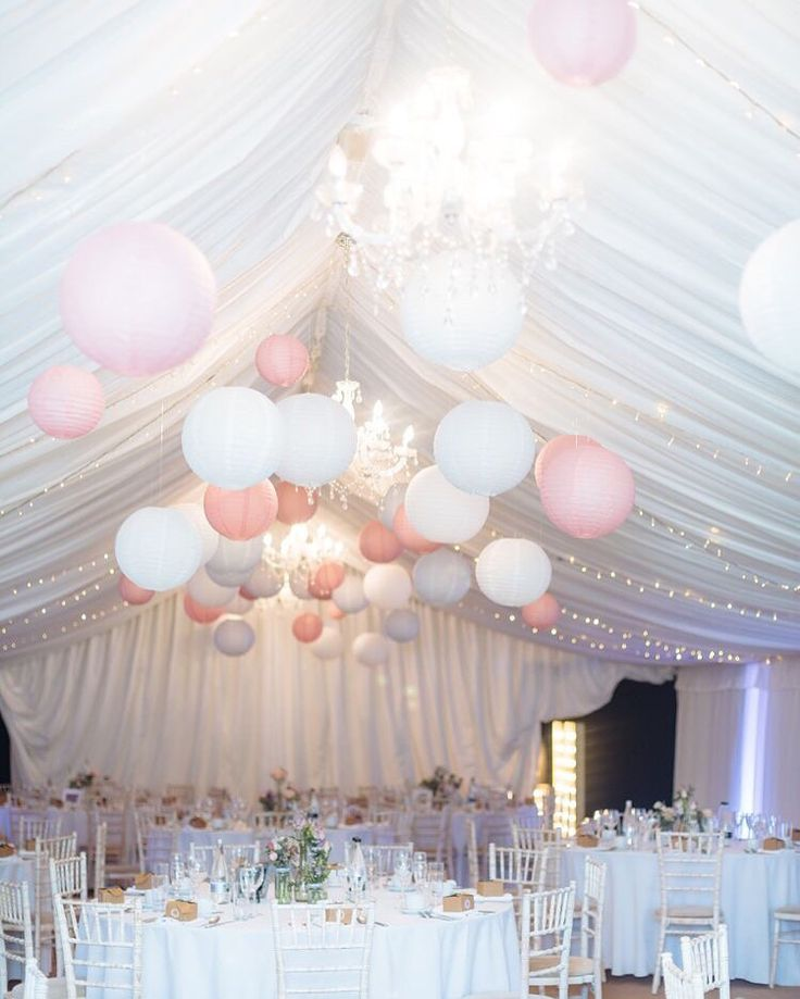 Licht roze en witte lampionnen in de feesttent. Light pink and white paper…