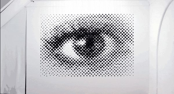 """Michael Murphy's """"Perceptual Shift""""—a 3D halftone sculpture of an EyE that was made with 1,252 wood balls, paint and braided fiber."""