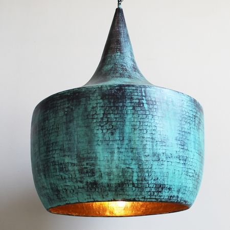 Hand pounded copper lantern with beautiful verdigris patina on the exterior with true copper finish on the interior. The copper and bulb reflection gives off a warm glow when turned on. This lantern comes with 3' of hanging chain.