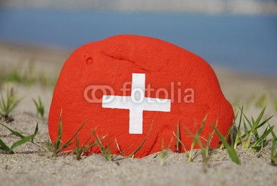 Flag of Switzerland on a stone over the sand