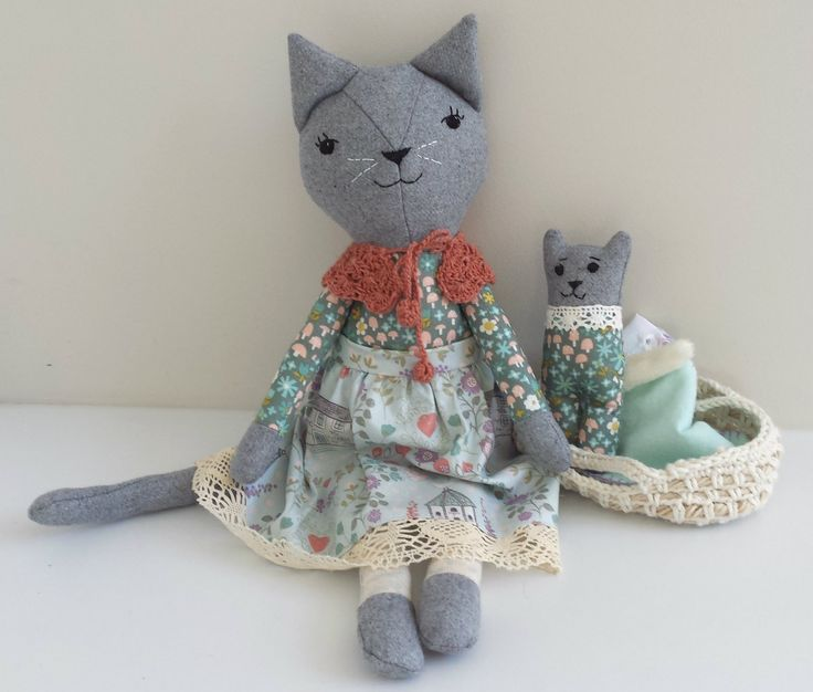 This cat doll is named Minnie.  She is a one of a kind, handmade doll and she has a kitten that likes to sleep in her Moses basket.This doll is stuffed with 1005 pure New Zealand wool stuffing.Minnie measures approximately 46 cm (18 inches) tall from tip of her ears to toes.She wears a removable skirt and hand made crochet wrap with pompom ties at the front.The kitten (approx. 6 inch), has a faux fur tail and comes with a Moses basket, and blanket.Minnie has buttons that...