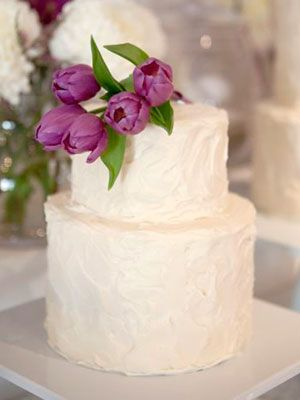 A simple buttercream wedding cake topped with fresh purple tulips.