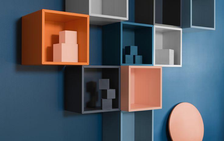Blå vegg med kvadratiske kuber i grått, oransje og blått.