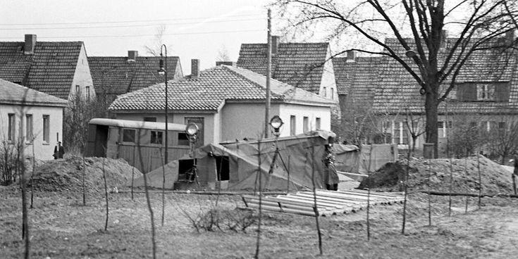 Ein Volkspolizist (rechts neben dem Zelt, bewacht eine Ausgrabungsstelle des US-amerikanischen Spionagetunnels im Ost-Berliner Stadtteil Altglienicke an der Grenze zwischen sowjetischem und US-amerikanischen Sektor, aufgenommen im April 1956. Foto:  Berliner Verlag/Archiv – Quelle: https://www.berliner-zeitung.de/28961034 ©2017