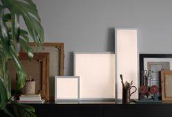 Skjenk med tre tente LED-lyspaneler i forskjellige størrelser, vist sammen med bilderammer, bøker og en kopp med malerpensler.