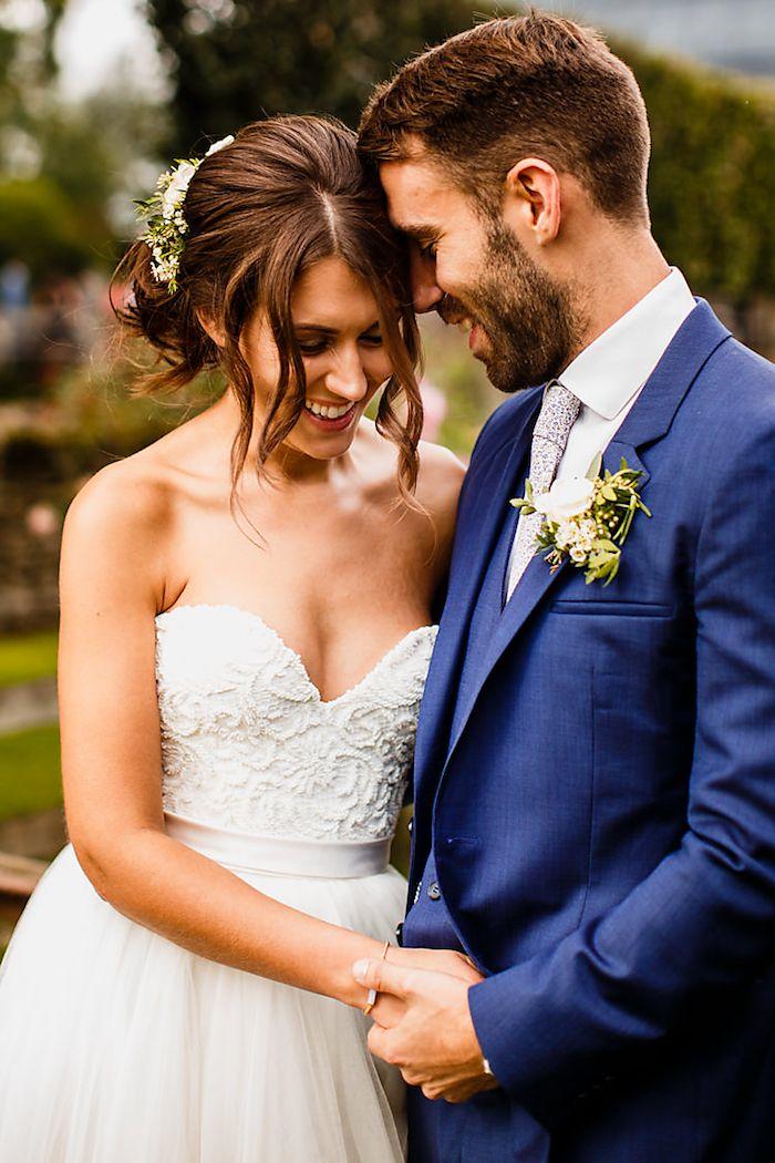 Elegante Hochsteckfrisur mit locker fallenden Strähnen, mit echten Blumen verziert, trägerloses Brautkleid, Oberteil aus Spitze und Tüllrock, der Bräutigam mit blauem Anzug und weißem Hemd