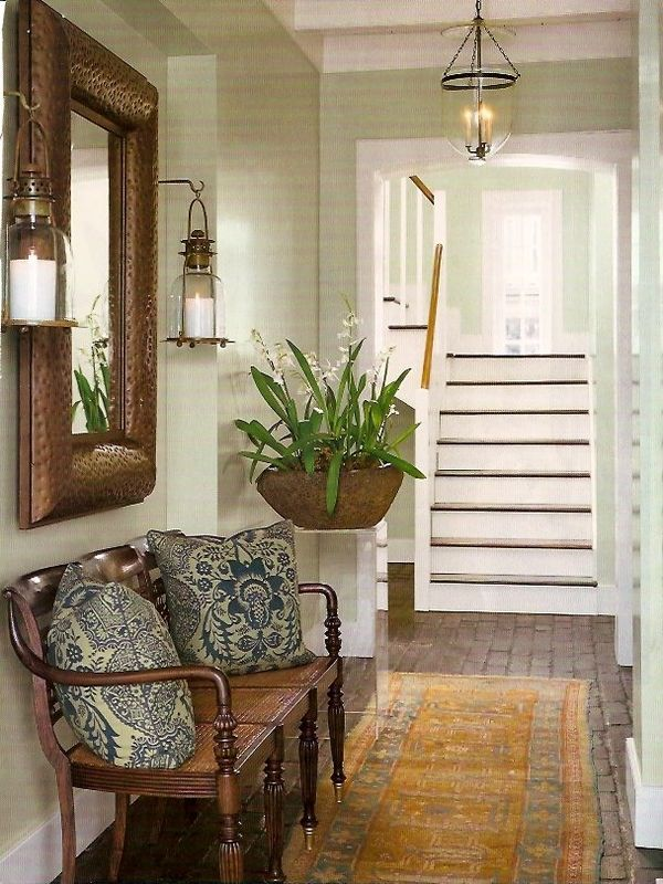 Lauren Leonard Interiors.  NOTES: love the nautical-style lanterns, the wood floor, the greenery, the exotic pillow prints, the uncluttered feel.  Would choose a slightly brighter rug.