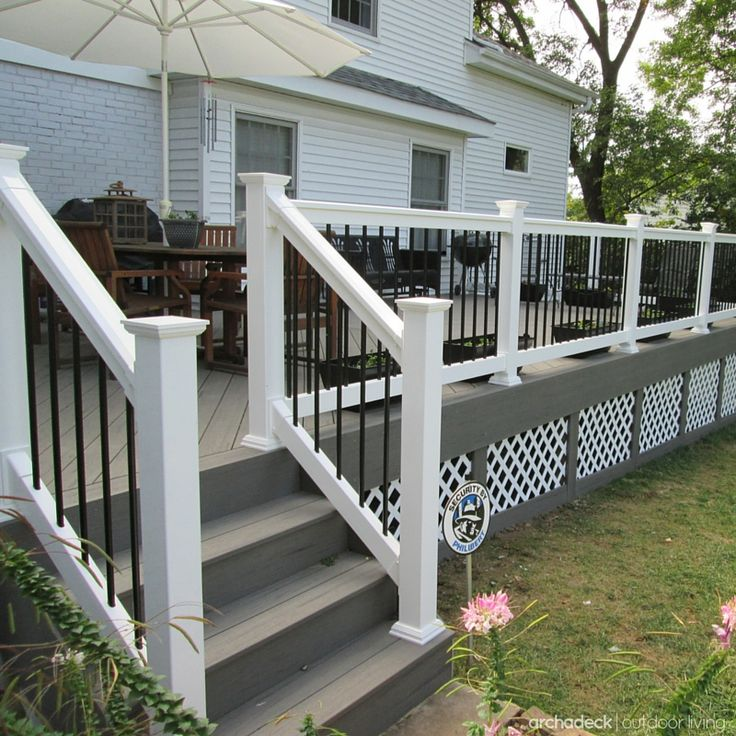 Raised slightly above-grade, this forever-fashionable gray deck was constructed using TimberTech state-of-the-art low maintenance materials, white vinyl rails with black metal balusters, a diagonal floor board pattern and under deck lattice trim. | west-county.archadeck.com