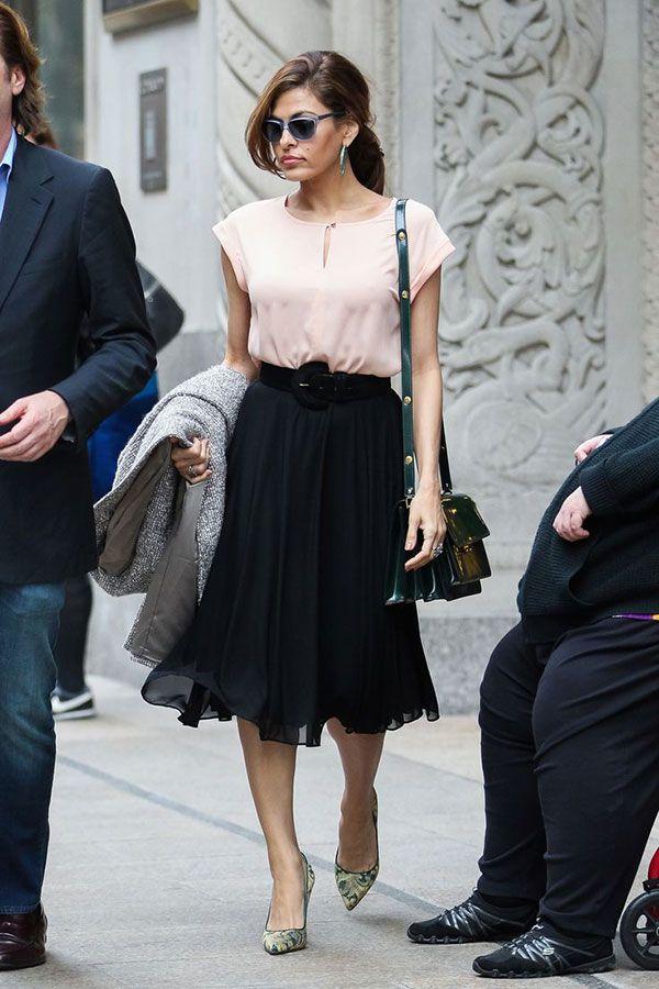 Eva Mendes combinou a saia midi com o cinto e uma blusa rosa millenial.