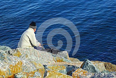 Fisherman on the lake, sea, ocean, hard stones. Person hobby fishing rod blue water copy space.