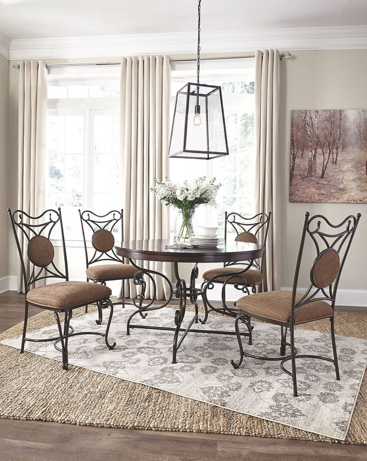 Brulind curved metal frame round dining table with four chairs and Aviana rug