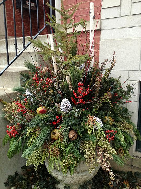 Christmas urn with very full mixed greenery, pine cones, ornaments, berries, twigs