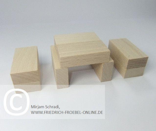 Tischgruppe aus Holzbausteinen natur mit Spielgaben nach Froebel (Spielgabe 4)