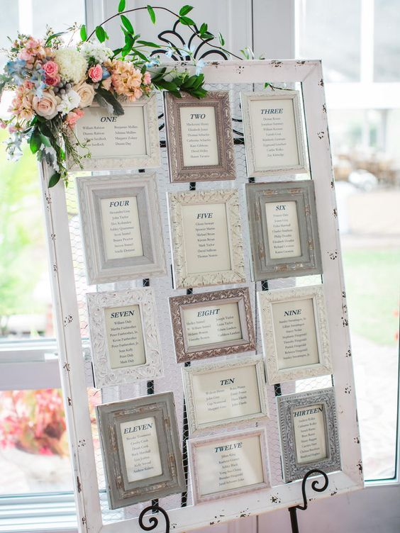 Seating chart at a wedding with chicken wire and frames mounted on it with table numbers