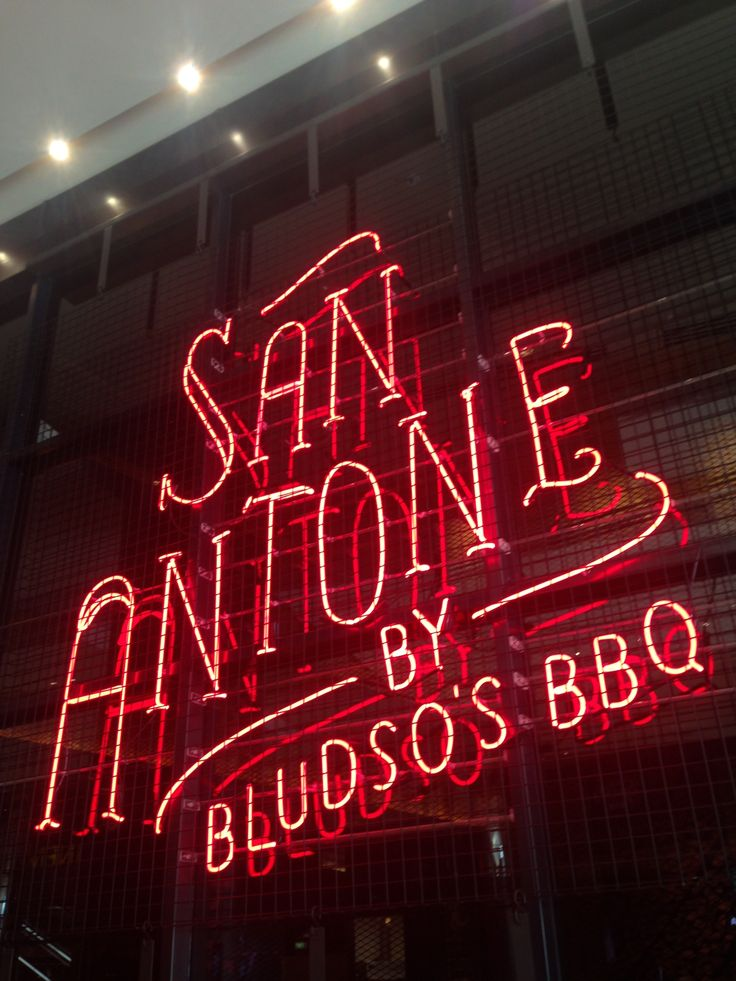 PHOTO 1: San Antone signage neon and metal grates. Mixes classic Western signage with modern caging on top.
