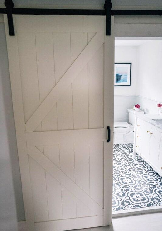 Jess Ann removed her old builder-grade door and replaced it with a white barn door with dark hardware. The sliding effect gives the room a more spacious feel and it's already primed and painted, so she saved on prep time.