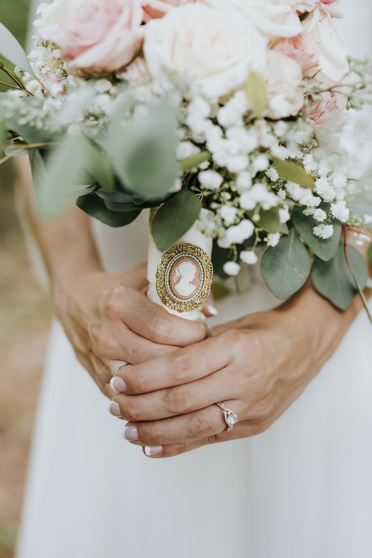 A beautiful family brooch was the perfect detail for this bride's pink and cream wedding day bouquet. Her bridal portraits were done in a stunning wooded area on family property in New Hill, NC, near Raleigh. Photo by Charlotte Wedding Photographer Kevyn Dixon.