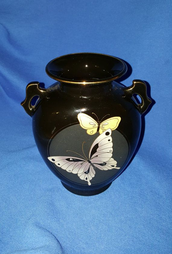 Gorgeous 1960s imported Japanese gold trimmed black vase featuring two beautiful butterflies in mid flight. The bottom of item is marked Fine China Japan in gold lettering. This piece will only enhance your wall unit , coffee table, shelf, or simply add it to your Asian vase collection. The piece itself is in excellent condition with no chips or cracks, only a few very minor surface scratches seen only on close inspection which do not detract from the piece. I ask that you inspect the…