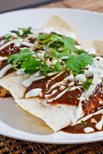 Enmoladas: Chicken Enchiladas drenched in a spicy, thick and chocolatey mole sauce served with onions, sour cream and queso fresco (mole sauce from site, chicken broth, shredded chicken, corn tortillas, sour  cream, onion, queso fresco or feta, cilantro and toasted sesame seeds)