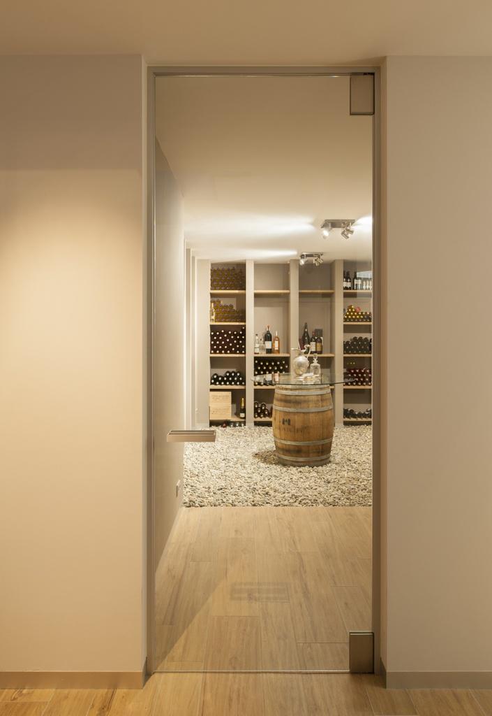 Goed afsluitende glazen deur op maat in een modern interieur. De glazen deur is voorzien van een afsluiting rondom de deur en is uitgevoerd in 10mm helder glas. Belgische fabrikant: http://www.anywaydoors.be