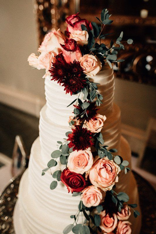 Buttercream wedding cake with cascading pink and burgundy flowers {Lunalee Photo…