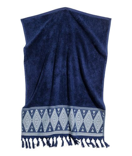 Mörkblå. En handduk i mjuk bomullsfrotté. Handduken har broderat mönster och tofsar nedtill. Hängare på ena kortsidan.