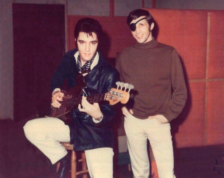 """Memphis Boys pianist, Bobby Wood, who lost his right eye in a horrific car crash, stands alongside Elvis Presley inside American Sound Studio in Memphis, TN, on January 13, 1969, the first night of Presley's sessions. The """"Promised Land"""" rocker clutches a 1959 Fender Precision bass used by session ace Tommy Cogbill. """"Kentucky Rain,"""" featuring harmony vocals and piano from Ronnie Milsap, would be waxed to vinyl the next month. Image Credit: Photography by Dan Penn / For Elvis CD Collectors…"""