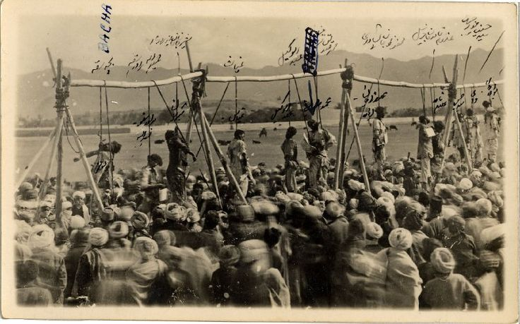 Photograph of a number of dead bodies, including that of Bacha i Saqao (far left) hanging by the neck from an crude gallows, in the foreground a large crowd of men and in the background cows, houses and mountains. Each of the bodies is labelled in Persian handwriting and that of Bacha in English, in ink, on the print.