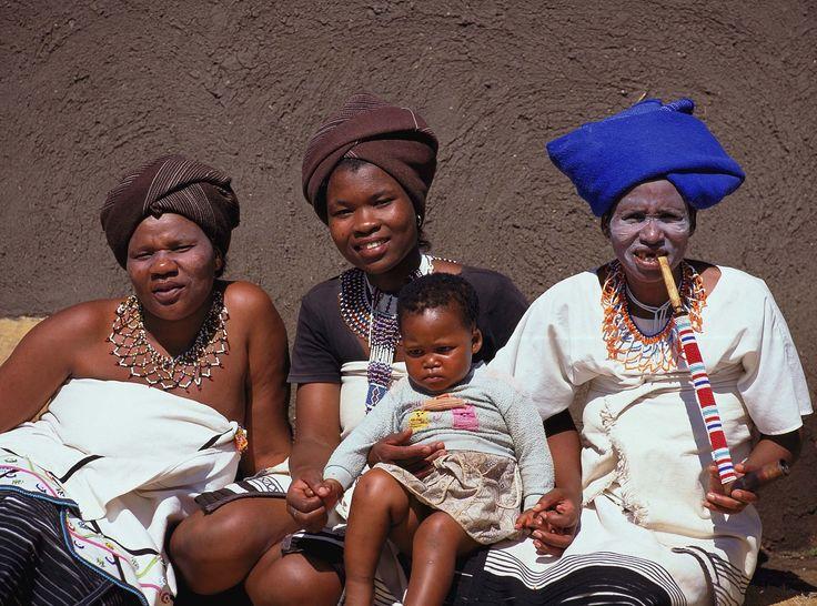Vier generasies van Xhosa-vroue in tradisionele klere, met ingewikkelde kralewerk-versierings
