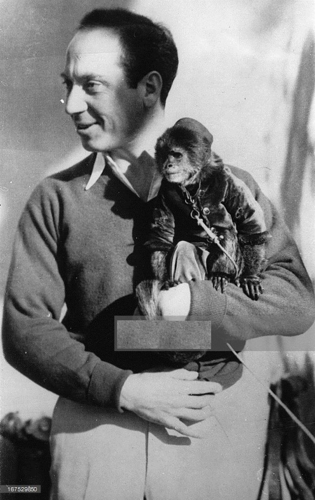 0 Harpo Marx without make-up holding a monkey on his arm