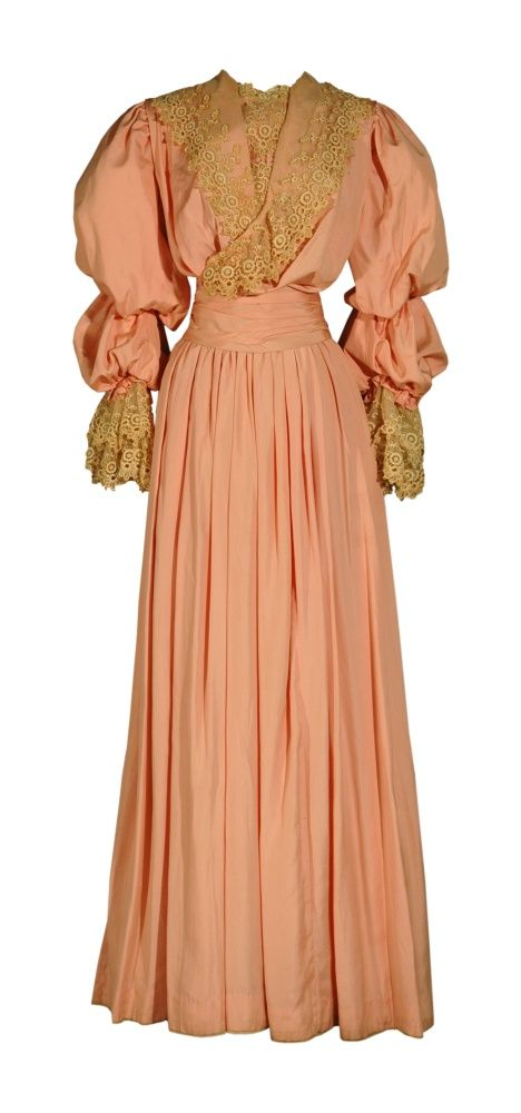 1905 Coral Silk Pouter Pigeon wedding dress. Rather than choose white for her wedding, Ellen May Smith wore this coral-colored frock when she married Ross Holland Jones in 1905. Her wedding ensemble also included a petticoat, gloves, and stockings, all of which are in the collections of the Kansas Museum of History. The bodice has the pouter pigeon front considered highly fashionable in the early 1900s. Its neckline is trimmed with wide bands of lace.