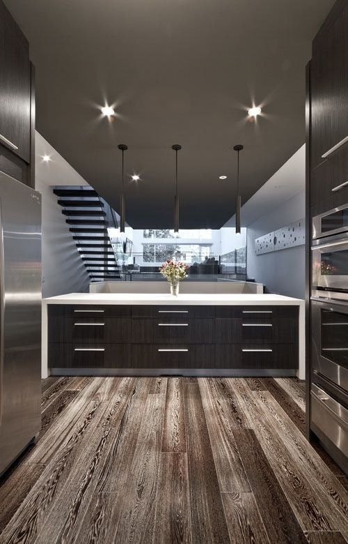 dark gray cabinets, white counters, stainless appliances, and big wide drawers. The stainless kick panel is a nice touch.