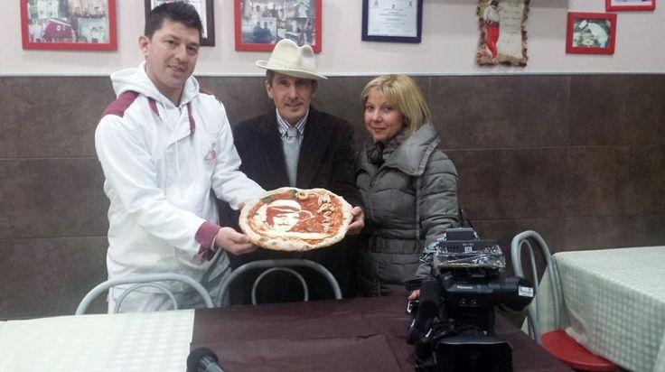 La consegna della pizza con l'immagine di Gennaro 'o masto d''a pizza da parte di Errico Porzio ideatore e realizzatore