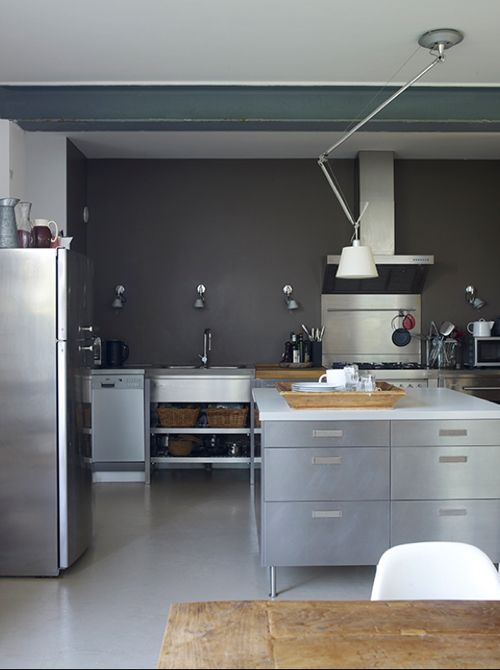 Cocina. Modern stainless steel kitchen with a kitchen island. Minimalist design, grey kitchen cabinets, appliances and grey walls. Love the spotlights on the wall.