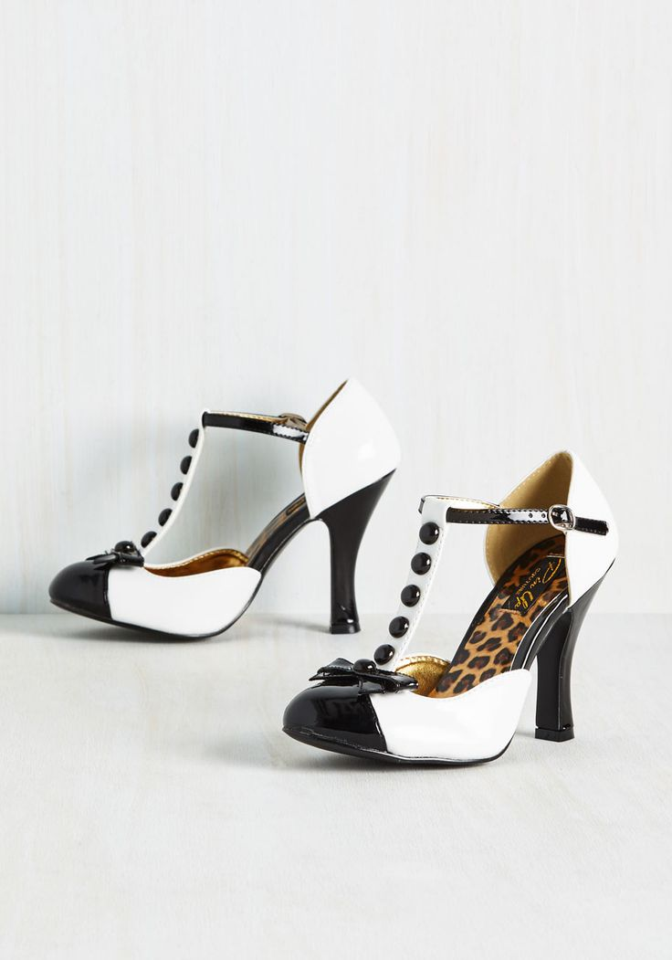 If you've been searching for the perfect pair of pumps, then you're in luck! Flaunting these black-and-white heels is the chance of a lifetime, for their glossy silhouette, T-straps, faux-buttons, and bow-topped toes design personify a fortune of fashionable finds!