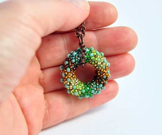 I love designing unique jewelry!    This beautiful round pendant cheery colors reminiscent of a jewel of a beautiful nymph.    Hand donut woven from seed beads in shades of sea foam, dyed topaz, matte topaz, gold, chartreuse and green.    This donut hang from a copper chain.    Measures:  Donut pendant: almost 30 mm (1.18) in diameter.  Necklace chain: almost 19 inches (48cm) in long.    How to mesure a necklace:  Take a wool strong and a meter, cut the strong at the measure I give you…