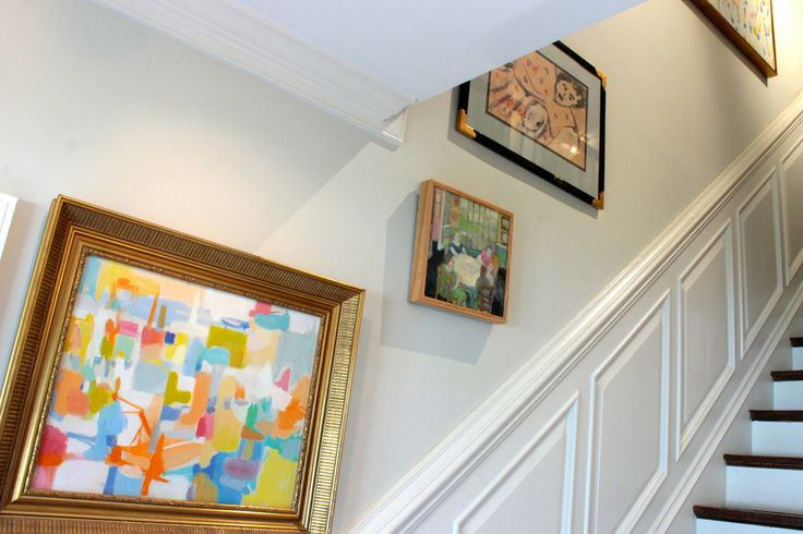 Paintings, including one by Helen Hattorf, grace the stairwell via The Gracious Posse