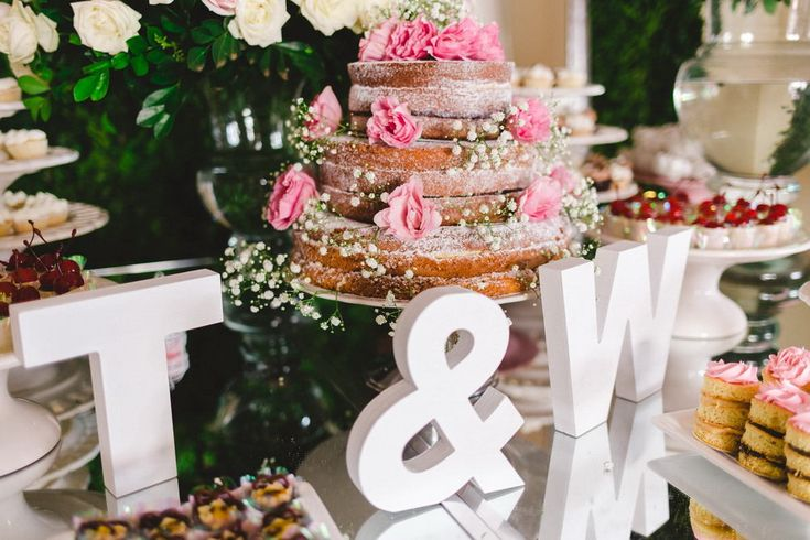 The candy table was adorned with flowers, their initials T and W and the middle of it was a spongy brown layered cake with sheer pink sugared dusting and various treats surrounding the centerpiece.