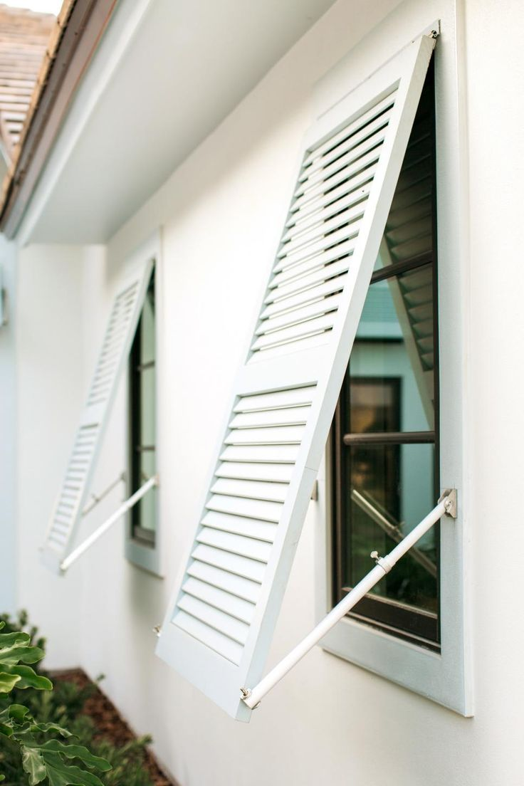 Painted cedar plantation shutters are functional. Mounted awning style, they help shade the interior from the Florida sun.