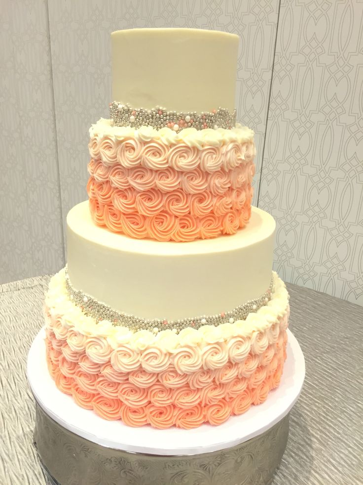 Silver and coral buttercream wedding cake with gorgeous rosettes and pearls.