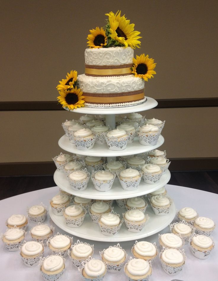 Sunflower wedding cake and Cupcakes! This is what I really am leaning towards...smaller cake for us to cut and cupcakes for guests so we can eliminate having cake cutters!