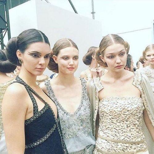 """Kendall Jenner, Lindsey Winxson et Gigi Hadid au défilé Chanel haute couture printemps-été 2016 regard yeux eye-liner graphique, coiffure cheveux en chignon """"croissant"""""""