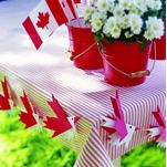 Canada Day decorations - love the red and white gingham table cloth, the red buckets with white flowers, birds are a craft made from red and white maple leaf shaped paper - pattern and instructions for making bird banner