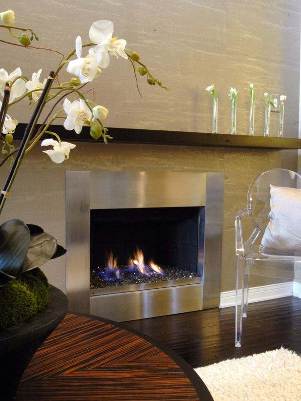 Designer's Notes Using a stainless steel surround, offset by a textured wall treatment and translucent chair, this residential fireplace evokes both modern and feminine design.