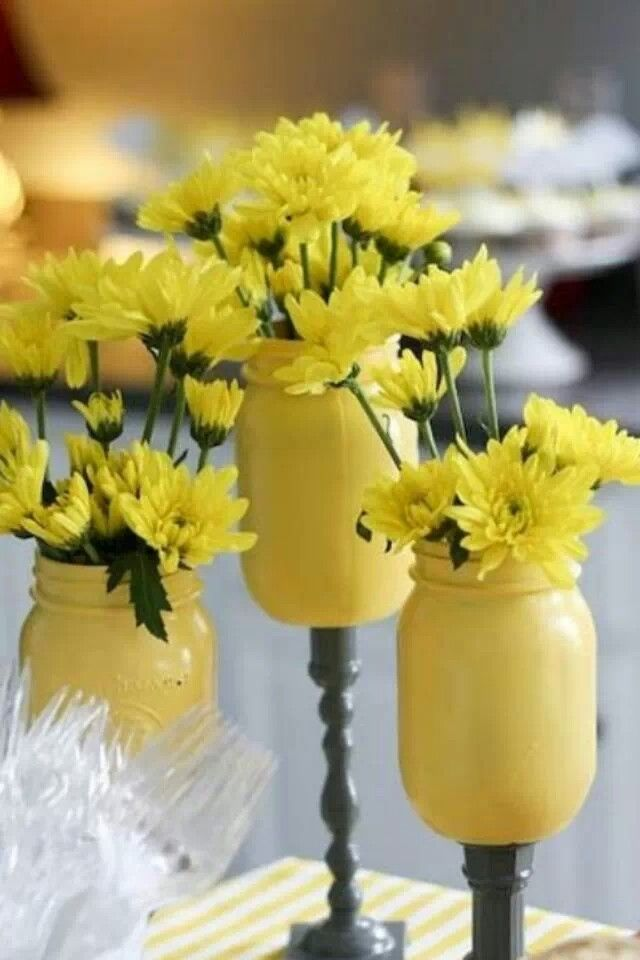 Too cute! Mason jars. Painted and glued to candle sticks then add flowers :)