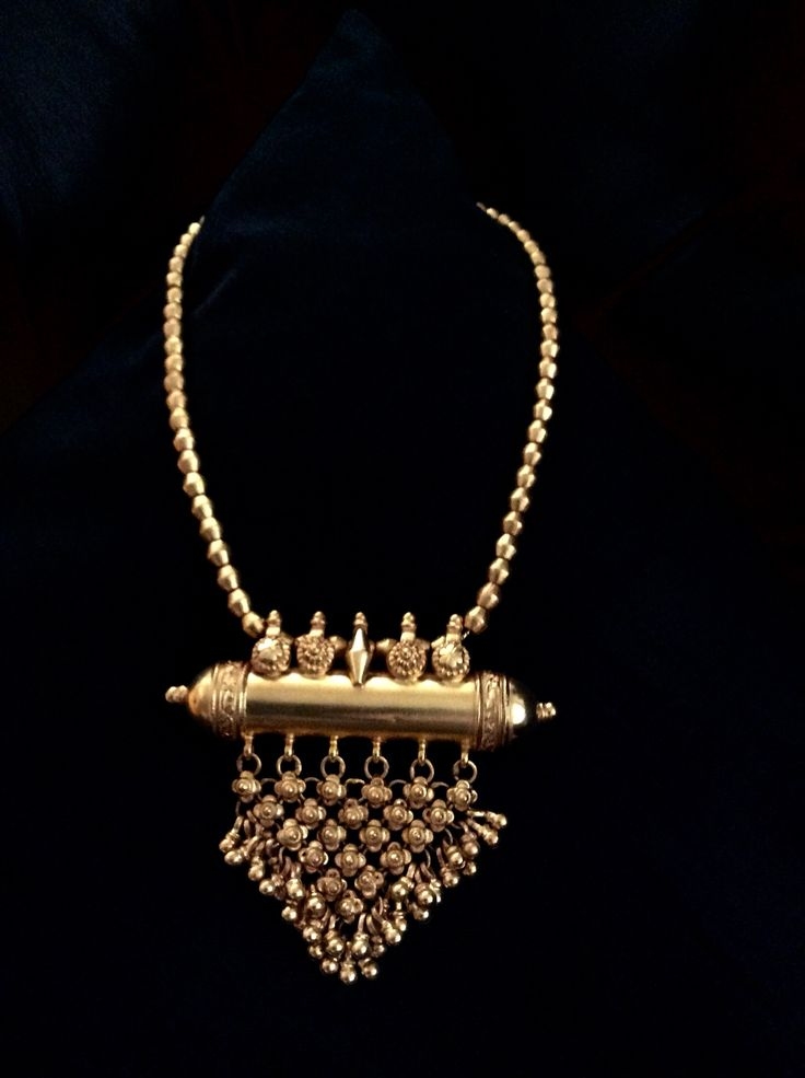 Antique gold Indian amulet pendant with gold bead necklace. The delicate amulet box,originally intended to hold the owner's protective amulet or prayer. Rajasthan,India.