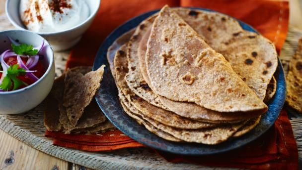 Chapatis can be reheated but they're best cooked fresh. You could also spread your favourite pickle or chutney over them and roll them into tortilla shapes.