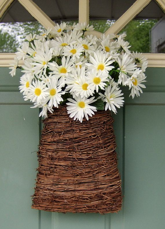 This is a basket filled with beautiful artificial white daisies. It is about 18 inches tall by 12 inches wide from the flower tip on one side to the